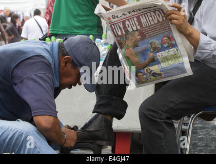 Mexico City, Distrito Federal, Mexico. 23rd June, 2014. A man reads La Prensa newspaper while he gets his shoes - Stock Photo