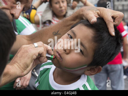 Mexico City, Distrito Federal, Mexico. 23rd June, 2014. A boy gets his face painted red, white and green at the - Stock Photo