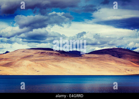 Vintage retro effect filtered hipster style travel image of Himalayan mountain lake in Himalayas Tso Moriri - Stock Photo