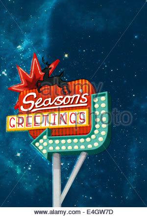 "Christmas ""Season's Greetings"" neon sign with reindeer and arrow - Stock Photo"