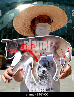 (140711) -- SEOUL, July 11, 2014 (Xinhua) -- An animal rights activist holds a placard during a protest against eating dog meat in front of the city hall of Seoul, South Korea, July 11, 2014. (Xinhua/Park Jin-hee)