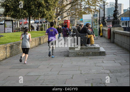 A young woman female and man male running along the River Thames on a Spring evening after work, London UK - Stock Photo