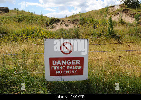 Danger warning sign on barbed wire on MOD land on walk to Ginst Point Pendine Carmarthenshire - Stock Photo