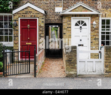 Typical Victorian terraced cottages with red and white doors and alley to back yard in Twickenham, Greater London, - Stock Photo