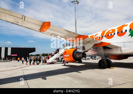Passengers boarding via front stairs to Easyjet plane. - Stock Photo