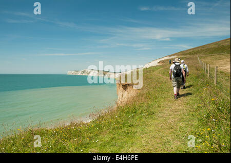 walkers hikers ramblers on the coastal path aft Afton down leading to freshwater on the isle of wight england uk - Stock Photo