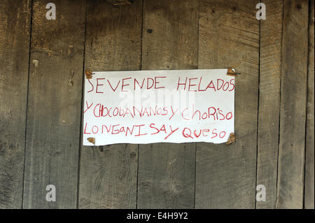 Handwritten sign outside a shop saying 'se vende helados y chocobananosy choriso longanisa y queso' Ice cream for - Stock Photo