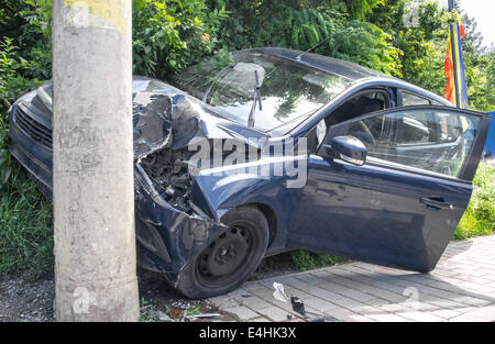 Hard crushed car in the city, frontal damage - Stock Photo