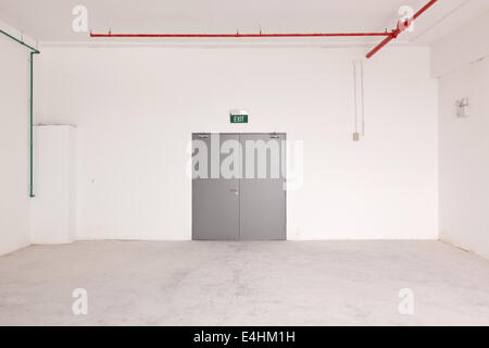 Interior of a bare, empty room with the door and exit sign - Stock Photo