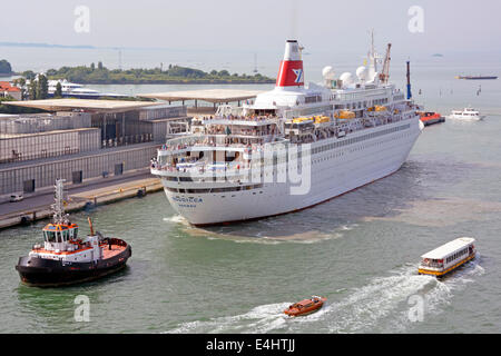 Passengers on deck of Fred Olsen Lines cruise ship liner Boudicca being towed backwards by tugboat to birth for - Stock Photo