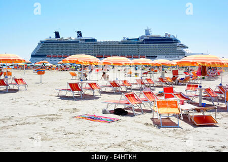 Colorful sun loungers and parasols on sandy beach short walk from cruise liner 'Celebrity Silhouette' docked nearby - Stock Photo