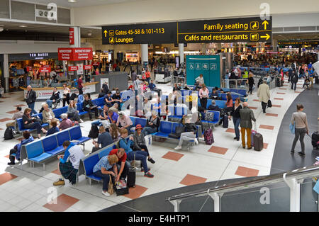 Family seating area & cafes restaurants signs at London Gatwick Airport North Terminal departure lounge and shopping - Stock Photo