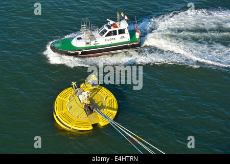Pilots boat passing cruise ships mooring hawsers on Floatex floating buoy anchored to sea bed - Stock Photo
