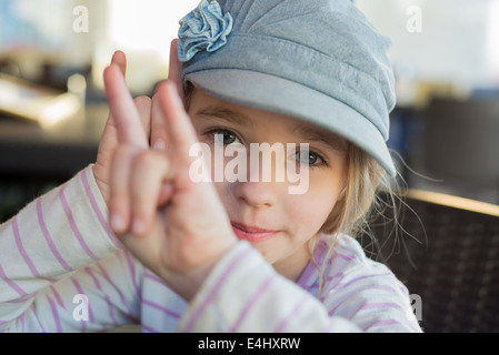 Cute girl showing horn signs - Stock Photo