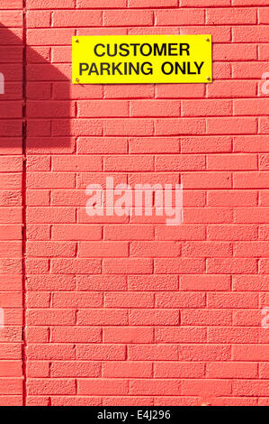 Yellow sign on a red wall saying 'Customer Parking Only' - Stock Photo
