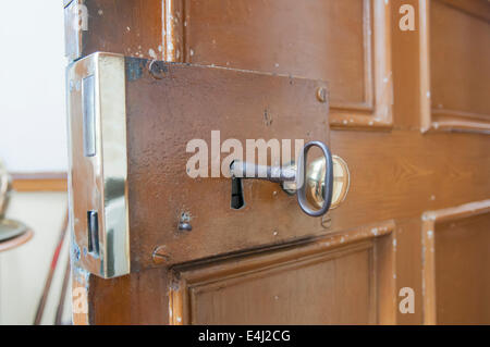 Heavy brass lock on the inside of a door, with a large old-fashioned key. - Stock Photo