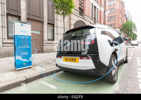 BMW i3 electric car plugged into a public charging station at a streetside parking bay. - Stock Photo
