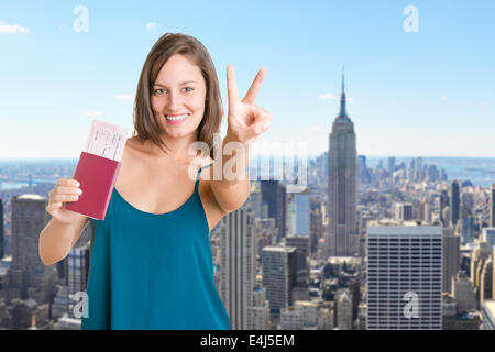 Happy young woman holding plain tickets and a passport, isolated in white - Stock Photo