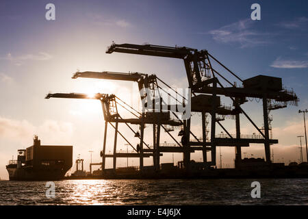 Cargo container ship approaching three giant container cranes at the Port of Oakland intermodal container terminal - Stock Photo