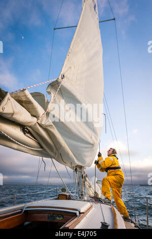 Sailor in yellow foul weather gear pulling on the halyard to raise the mainsail as he heads into cloudy weather - Stock Photo