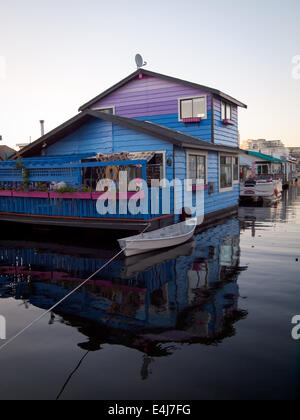 A view of colourful houseboat (float home) and canoe moored at Fisherman's Wharf in Victoria, British Columbia, - Stock Photo