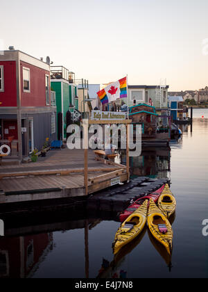 A Canada Gay Pride Flag flies over houseboats and kayaks moored at Fisherman's Wharf in Victoria, British Columbia, - Stock Photo