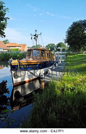 The classic motorlaunch Kaiser Wilhelm is anchored in the Elisabethfehn Kanal, Niedersachsen, Deutschland. - Stock Photo