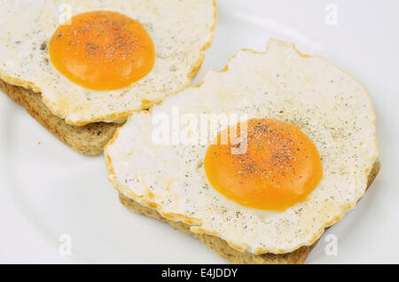 two fried eggs with salt and pepper on toast, close up on white plate, full frame - Stock Photo