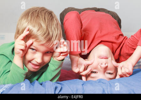 Two boys pulling faces (5-7 years). - Stock Photo