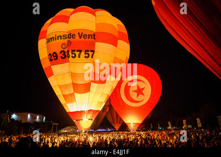 Igualada, Spain. July 12th, 2014: Thousands enjoy the glowing Hot air balloons in the night of Igualada as they - Stock Photo