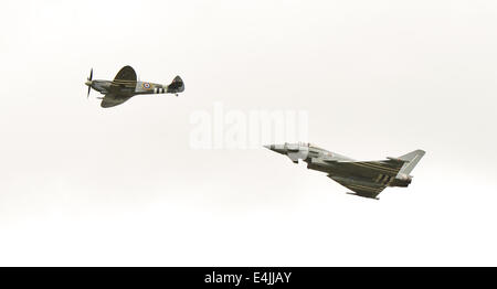 Fairford, UK. 13th July, 2014. Fairford Airshow 2014 Eurofighter Typhoon chasing WW2 Spitfire at the International - Stock Photo