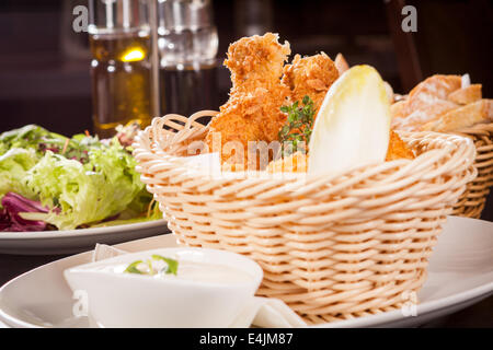 Crisp crunchy golden chicken legs and wings deep fried in bread crumbs and served with a bowl of dip in a wicker - Stock Photo