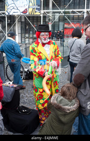 Paris, France - Clown in the Pompidou area  making balloon models for children - Stock Photo