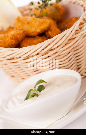 Crispy fried crumbed chicken nuggets in a wicker basket served as a finger food or appetizer with a creamy dip in - Stock Photo