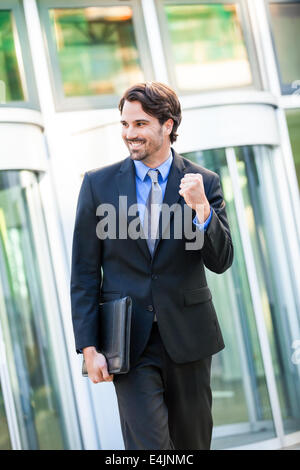 Motivated handsome young businessman leaving his office building with a briefcase under his arm punching the air - Stock Photo
