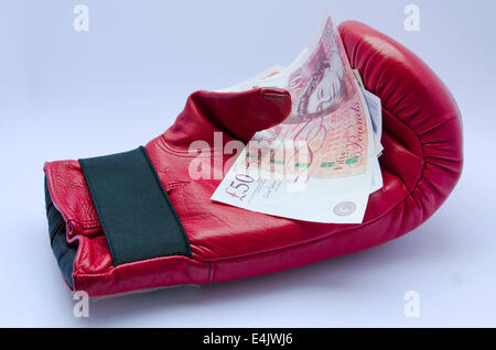 Red Boxing glove with pound notes on white background - Stock Photo