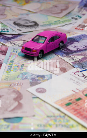 Pink toy car with pound notes - Stock Photo