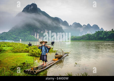 Cormorant fisherman and his birds on the Li River in Yangshuo, Guangxi, China. - Stock Photo