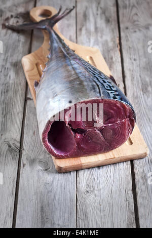 Fresh raw tuna tail on wooden board. Selective focus. - Stock Photo