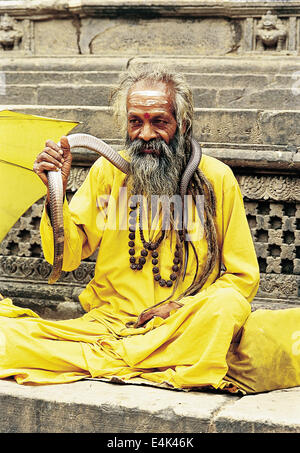 Kathmandu, Nepal - September 09, 2009: Portrait of Sadhu wiht a snake sitting outside one of the temples at Patan - Stock Photo