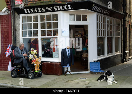 Mobility vehicle disabled older elderly man Margate Kent outside Charity shop for Pilgrims Hospices. 2014 2010s - Stock Photo