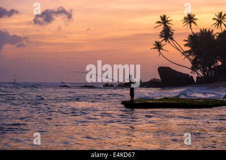 A fisherman, palm trees and rock in silhouette at sunset on a beach at Unawatuna on the Western coast of Sri Lanka - Stock Photo