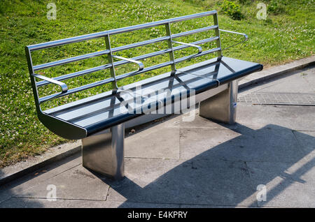 Modern public bench seat in an English town which is easy to maintain and is self-cleaning - Stock Photo