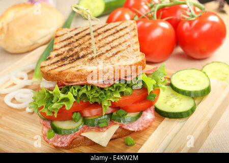 Sandwich with cheese and salami on wood background - Stock Photo