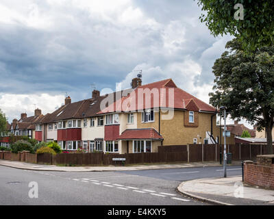 Typical English brick and tile houses in a residential suburban street with storm clouds - Twickenham, Greater London, - Stock Photo