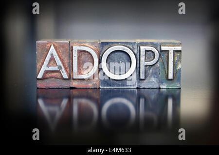 The word ADOPT written in vintage lead letterpress type - Stock Photo