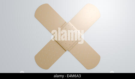 Two regular sticky plasters criss crossed on an isolated white studio background - Stock Photo