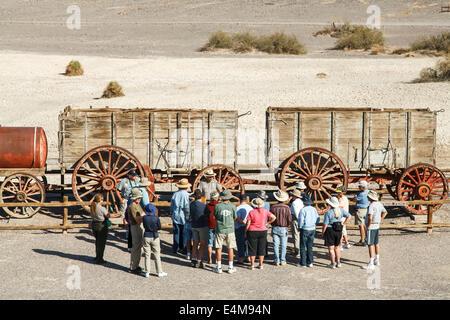Ranger-led tour at twenty mule team wagon, Harmony Borax Works Interpretive Trail, Death Valley National Park, California - Stock Photo