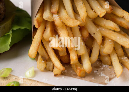 French Fries close up with pickle & lettuce detail from burger. - Stock Photo