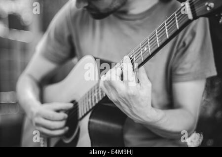 Young Man Looking Down Playing Acoustic Guitar - Stock Photo